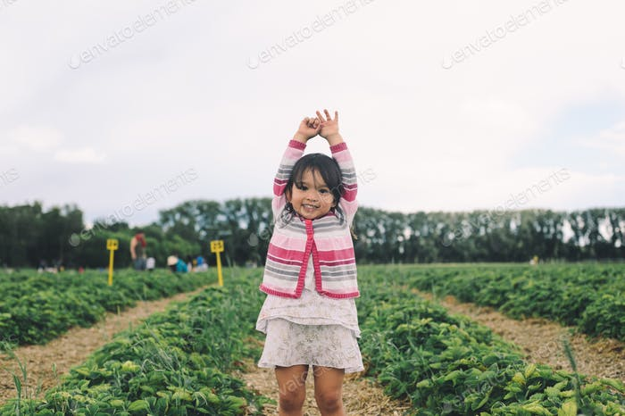 Happy excited girl in strawberry field with raised arms