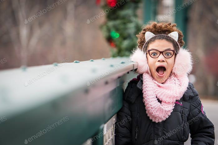 Excited little girl wearing her winter coat and ear muffs on a bridge