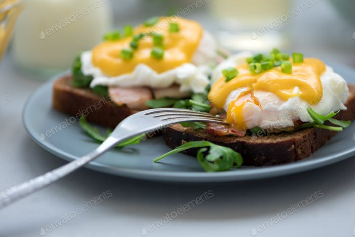 Close up eggs Benedict with arugula, bacon and hollandaise sauce on gray wooden background