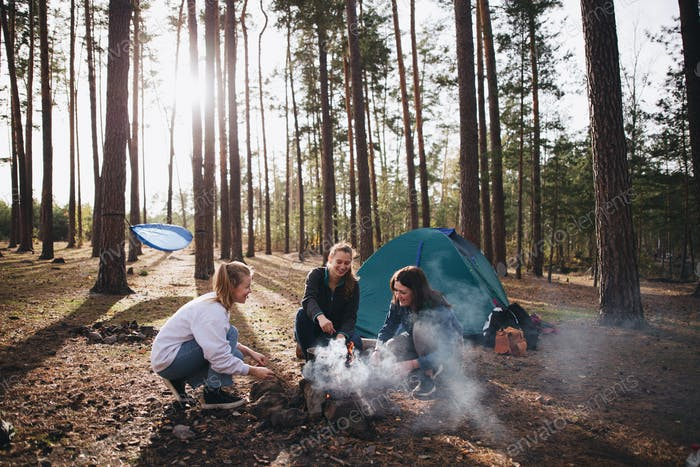 Three beautiful girls camping next to a fire in front of the tent in the forest during the beautiful