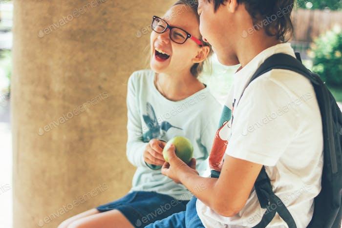 Two tweens girl and boy friends having fun near school