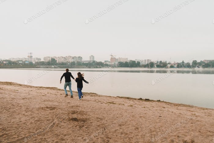 Man with his woman run near lake at empty morning coastline holding hands, family fun, happy couple