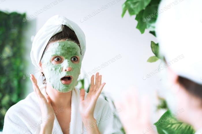 Beautiful young woman applies moisturizing green bubble face mask. Looking in mirror in white bathro