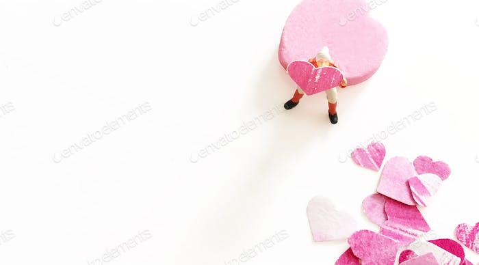 Tiny HO-scale man sitting on pink candy heart and holding small paper cut hand painted heart shape