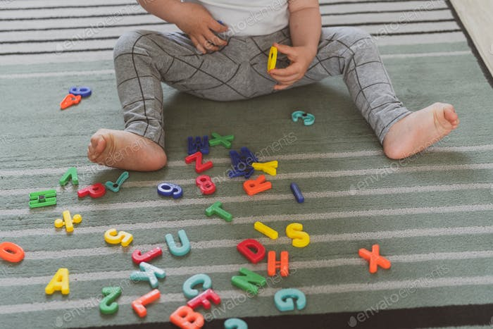 little cute toddler playing with toy letters sitting on the floor in livingroom