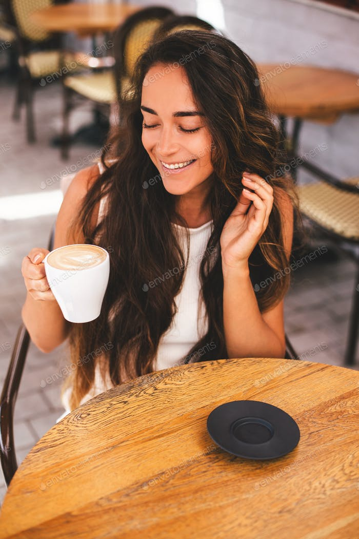 Young beautiful woman with long curly hair enjoying morning coffee in a cafe.