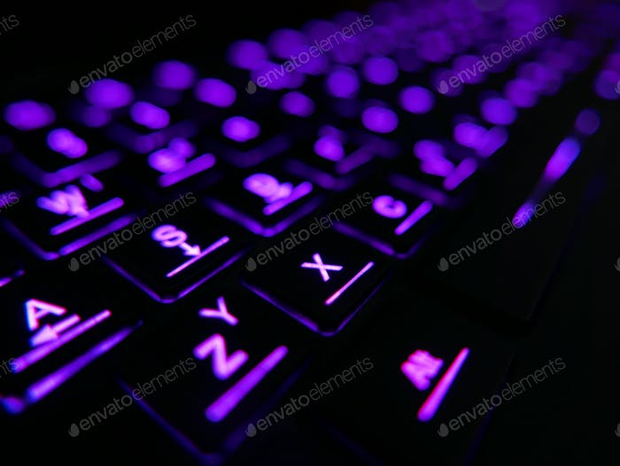 A computer keyboard with purple illumination.