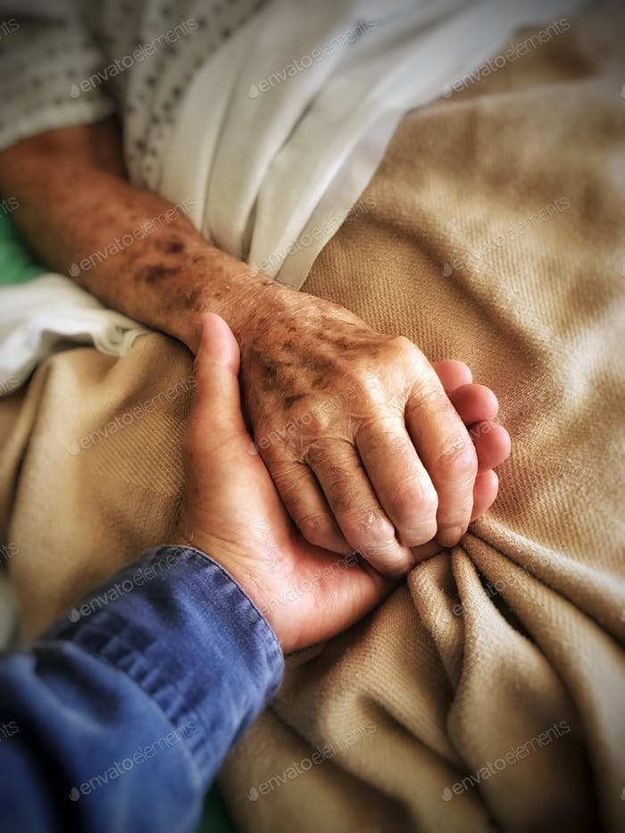 Son holds his dying father's hand at hospital bedside