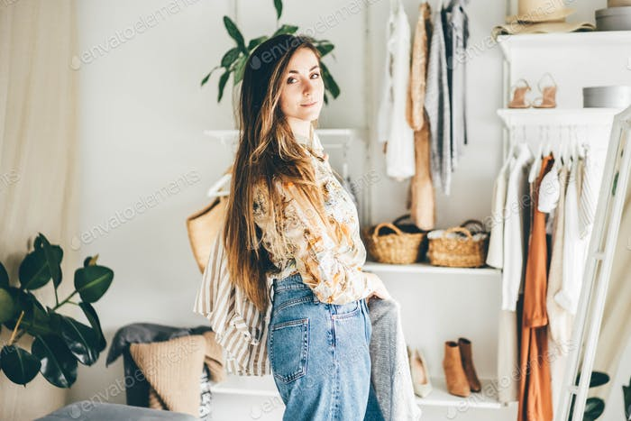 Long haired brunette woman chooses clothes in the wardrobe at home.