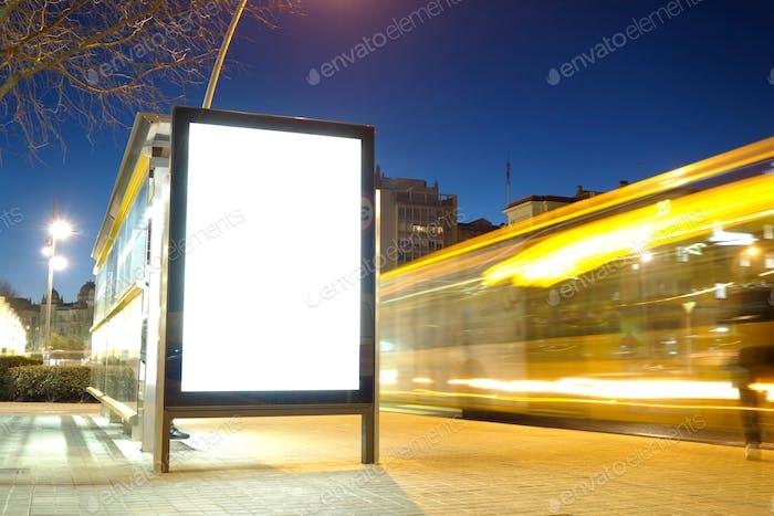 Blindwerbung in einer Bushaltestelle mit verschwommener Ampel in der Nacht