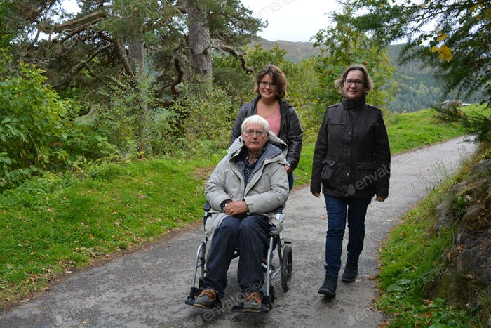 Acts of support and kindness, Family going for a walk, with senior man in a wheelchair
