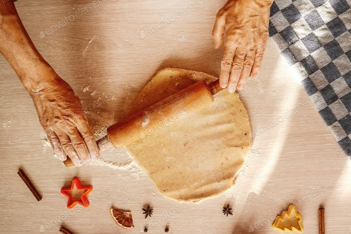 hands roll the dough with rolling pin