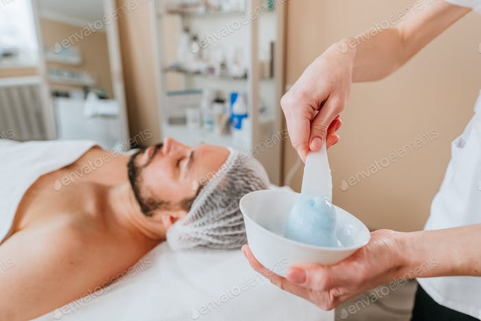 Esthetician making facial cleansing procedure using algae mask for a man