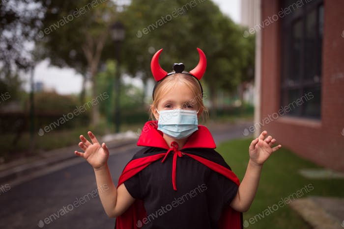 Happy kid in evil costume celebrating Halloween 2020 during coronavirus covid-19 pandemic