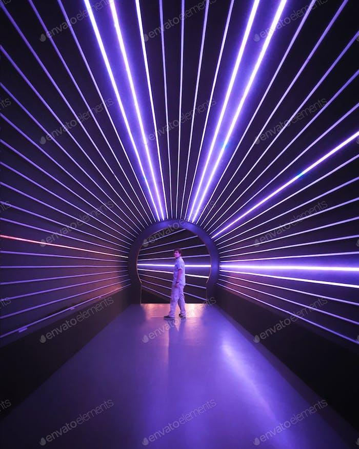 Un tipo en el túnel de luz de neón púrpura