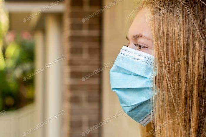 Ein Mädchen mit einer Einweg-Gesichtsmaske draußen. Obligatorisch, verpflichtend. Coronavirus und COVID-19