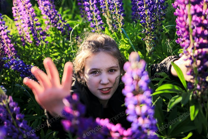 Beautiful young teenager girl in a field among blooming purple