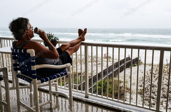 Active babyboomer drinking coffee in morning off his condo deck at the beach....