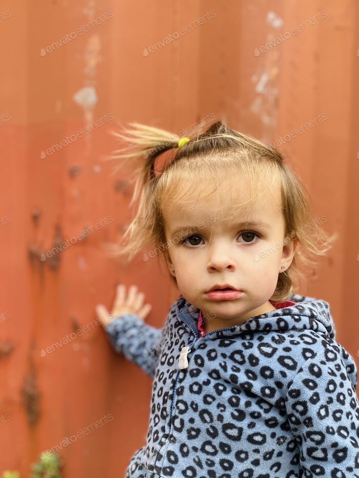 A young girl with a blank expression.