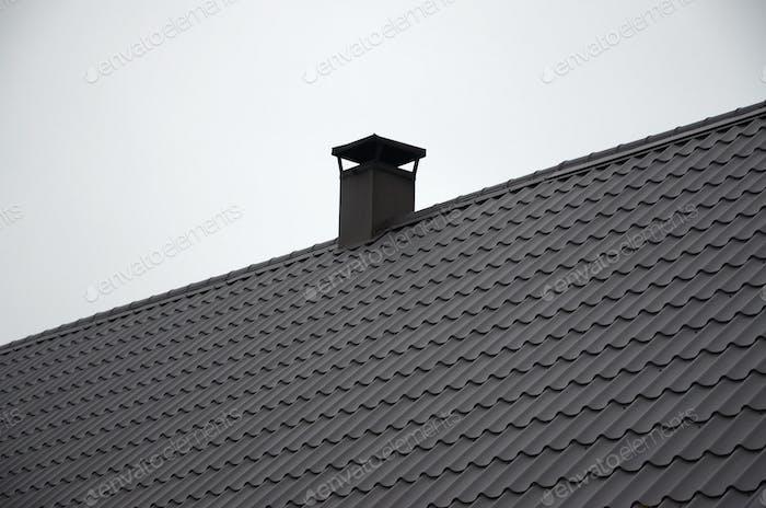 Modern brown roof made of metal. Corrugated metal roof and metal