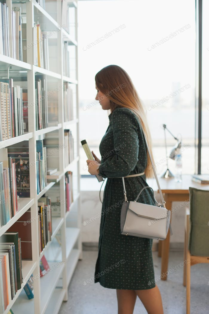 Woman with a book near bookshelves at public library