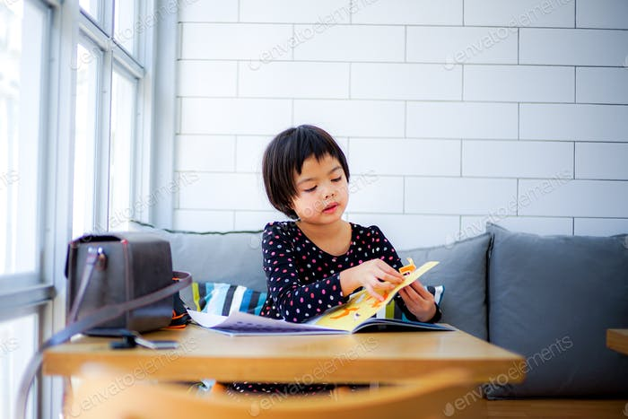 Asian little girl sits in the cafe and plays the sticker book with white wall tile in background