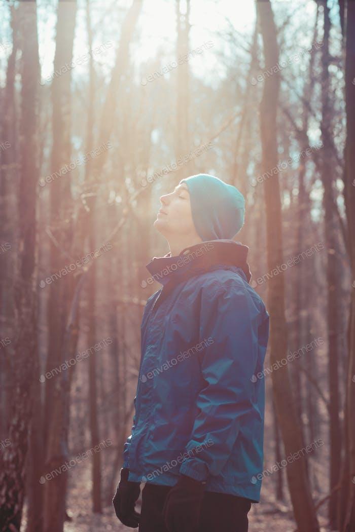 Молодой человек отдыхает на открытом воздухе во время тренировки в лесу среди безлиственных деревьев на холодную заморозку осенью