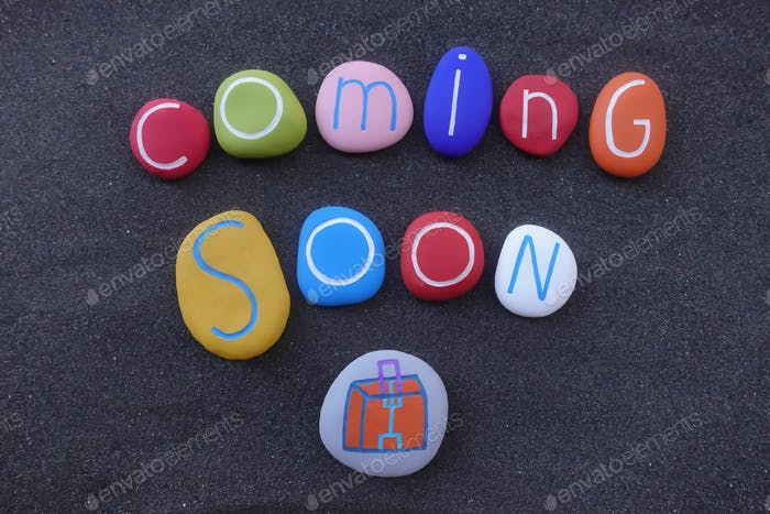 Coming soon text with colored stones design over black volcanic sand