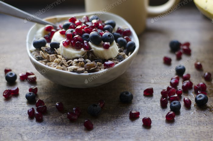 A bowl of cereal with blueberries and pomegranate seeds scattered around.