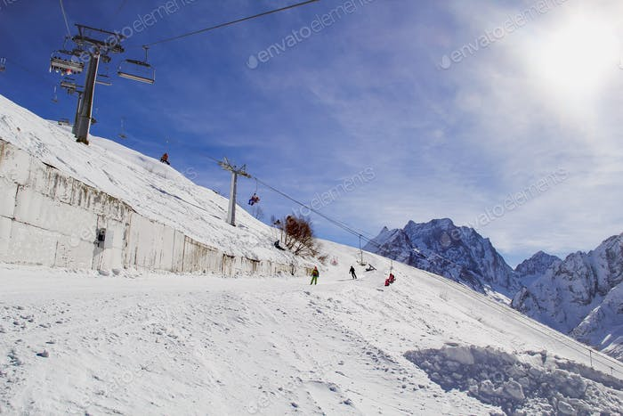 People skiing in the Caucasus mountains in the sunny weather with ski lift the background