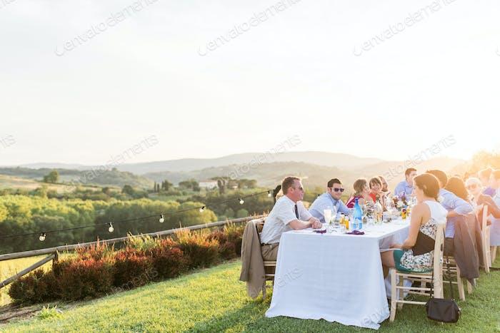 Millennials essen zusammen. Atemberaubende Aussicht in der Toskana, Italien um Sonnenuntergang.