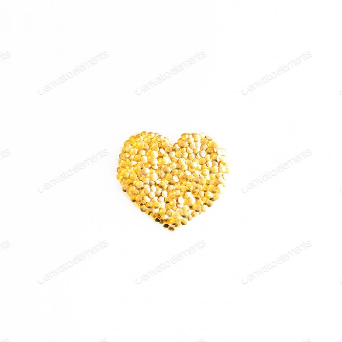 Heart shape made from shiny metallic brass tacks on a white background.