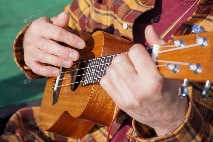 Человек играет на укулеле