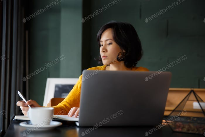 Young business woman in yellow dress sitting at table in cafe and writing in notebook. student, comp