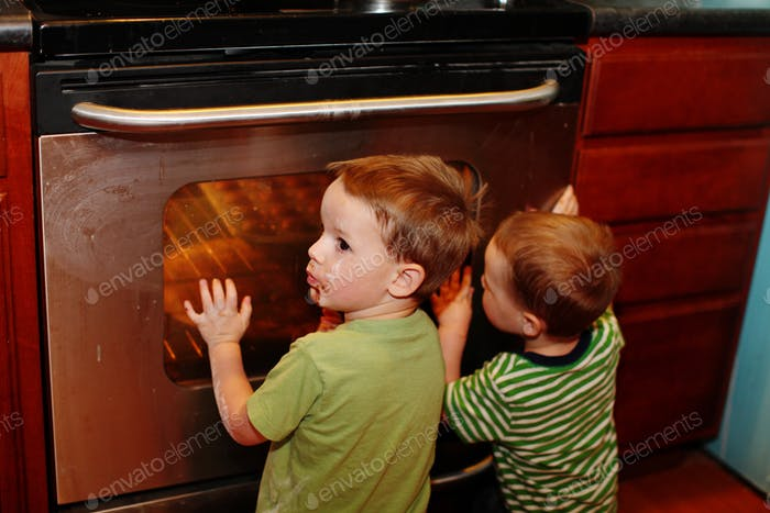 two boys wait anxiously for cupcakes to bake in the oven