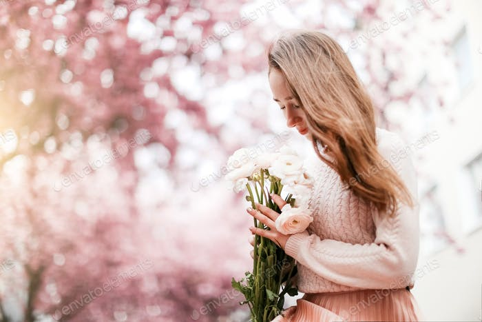 Beautiful girl in a pink sweater and pleated skirt sitting in a blooming pink cherry garden with a