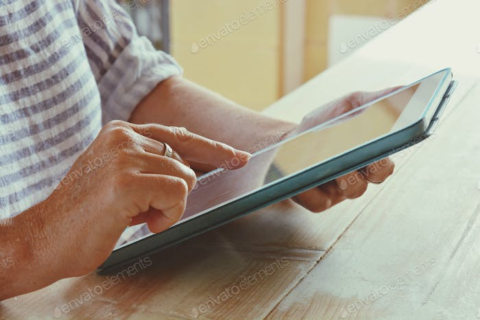 Woman using a digital tablet, selective focus, finger on touchscreen