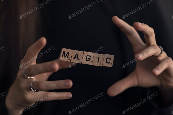Magic hands fingers wooden squares with letters