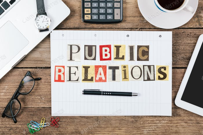 Public Relations title from newspaper cutout letters on paper notepad