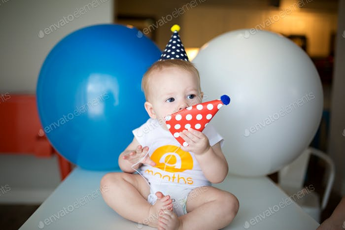 baby boy wearing a birthday hat with giant blue and white balloons