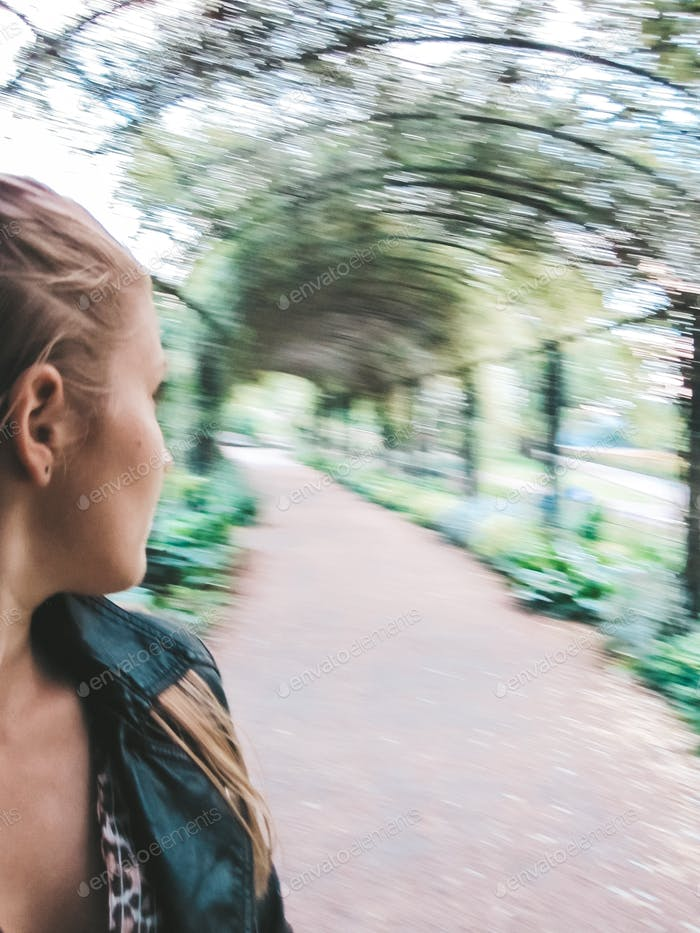 Woman looking back into the vertigo tree tunnel