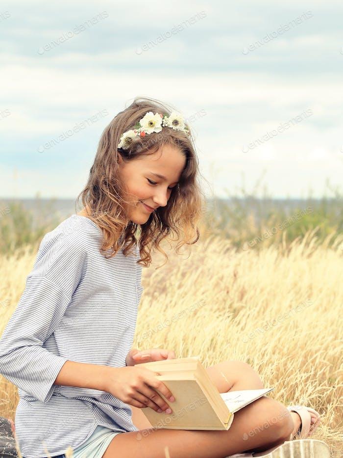 Schöne lächelnde Mädchen ein Buch lesen