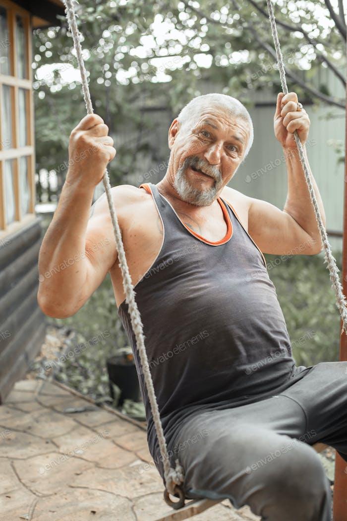 Baby boomer , grandpa swinging on a swing