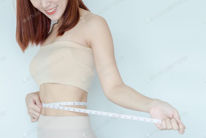 Close up of happy woman measuring her waistline . Perfect Slim Body