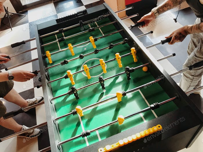 Men playing table soccer