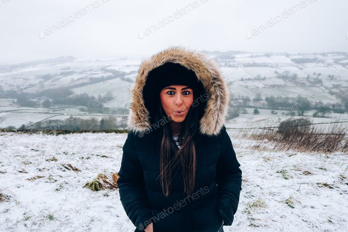 Beautiful young girl in the snow in winter clothes, in Yorkshire United Kingdom