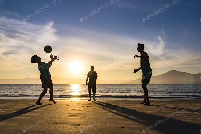 People playing football at beach