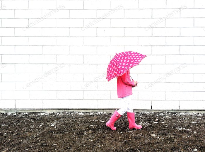 Girl walking in the rain with a pink umbrella and pink boots