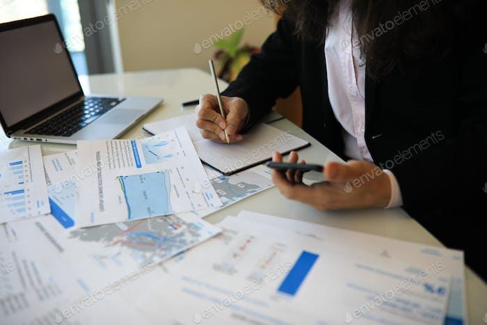 Junger Mann, der an seinem Schreibtisch arbeitet und Informationen am Telefon mit den Informationen in der Journa vergleicht
