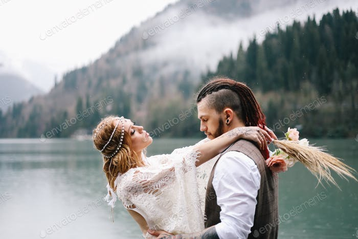Stylish boho wedding on the shore of the lake near the mountains and the forest in nature outdoors